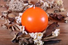 Orange Candle And Dried Plants Royalty Free Stock Photo