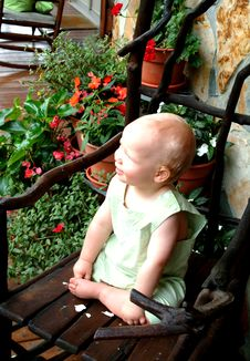 Baby With Flowers On Porch Royalty Free Stock Image