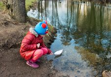 Little Girl Let A Paper Boat On The River Outside Stock Image