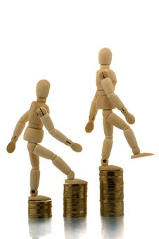 Manikins Falling Off Coin Piles Royalty Free Stock Image