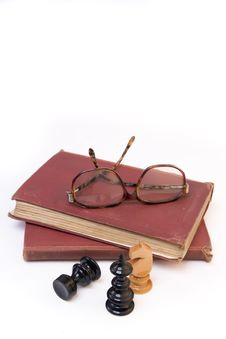 Chess Pieces With Old Book And Eyeglasses Stock Photo