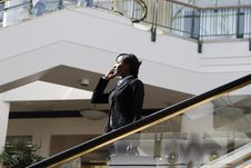Businesswoman On Phone On Escalator - Horizontal Stock Photo