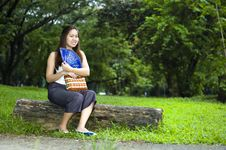 Happy Woman Sitting On Log With Blue Fan Stock Photography