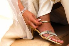 Free Bride In Brides Dress Putting On Sandal Stock Photo - 5297910