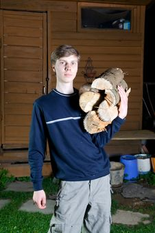 The Young Guy With Fire Wood Stock Photo