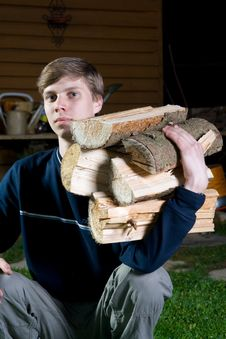 The Young Guy With Fire Wood Royalty Free Stock Images