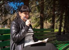 Free Beautiful Woman Sitting On A Park Bench Holding A Pen And Notebo Royalty Free Stock Image - 53378216