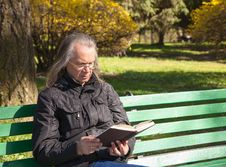 Haired Elderly Man Reading A Book Sitting On A Bench In City Par Stock Image