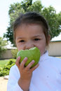 Free Little Girl Eating A Green Apple Stock Images - 5347884