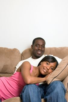 Couple Sitting On Sofa - Smiling Stock Photos