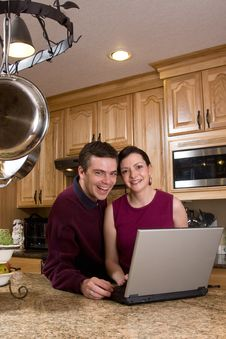 Couple With Laptop In Kitchen - Vertical Royalty Free Stock Photography