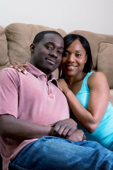 Free Couple Sitting By A Sofa Smiling- Vertical Royalty Free Stock Photography - 5365907
