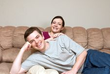 Happy, Laughing Couple Sitting On Couch - Horizo Royalty Free Stock Photography