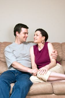 Happy Couple Hugging On A Couch - Vertical Royalty Free Stock Image