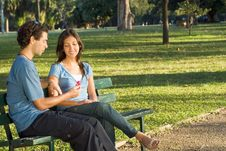 Couple In The Park Looking At Flower - Horizontal Royalty Free Stock Photography