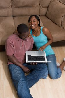 Free Couple Sitting In Front Of Couch With Laptop Com Stock Photography - 5434232
