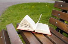 Free Open Book In The Red Cover Lies On A Park Bench Stock Photography - 54389652