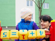 Free Mom Teaches Daughter To Be Considered With Wooden Cubes Stock Photography - 54502232