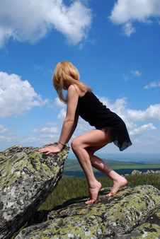Woman In The Black Dress On Rock Royalty Free Stock Image