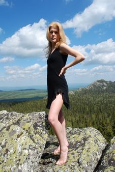 Woman In The Black Dress On Rock Royalty Free Stock Photo