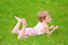 Free Little Girl Lies On Grass On Belly Stock Photography - 5470262