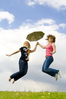 The Two Young Girls Jumping With A Umbrella Royalty Free Stock Images