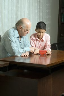 Grandfather And Grandson Are Sitting At The Table Royalty Free Stock Image