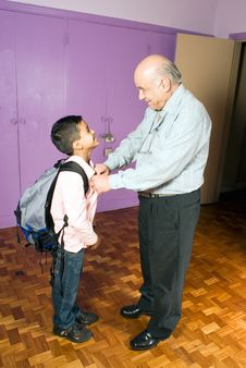 Free Grandfather Helping Grandson Leave For School Stock Photography - 5479142