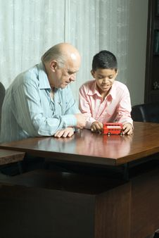 Free Grandfather And Grandson Looking At A Toy-Vert Stock Images - 5479234