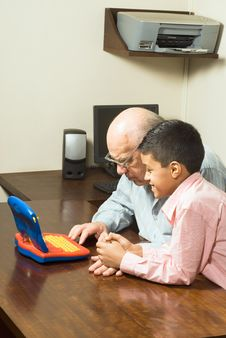 Free Grandfather And Grandson Looking At A Toy Computer Royalty Free Stock Photography - 5479967