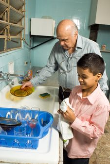 Grandfather And Grandson Washing Dishes - Vertical Royalty Free Stock Photography