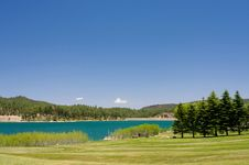 An Image Of A Aqua Lake Near A Golf Hole Royalty Free Stock Photography