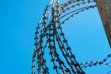 Free Coil Of Barbed Wire On A Concrete Fence Royalty Free Stock Photos - 55069098