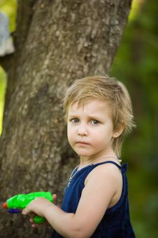 Little Girl Plays Near A Tree Royalty Free Stock Image