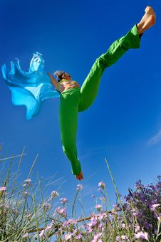 Girl With Blue Silk Scarf Jumping Stock Image