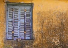 Blue Window Shuttered On Yellow Wall. Stock Photo