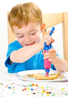 Free Boy Decorating Baked Biscuits Royalty Free Stock Photography - 5542827