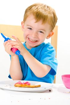 Boy Decorating Baked Biscuits Stock Image