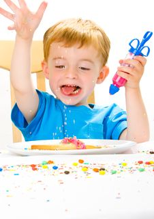 Boy Decorating Baked Biscuits Royalty Free Stock Images
