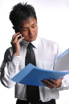Free Asian Business Man Looking At File With Phone Royalty Free Stock Photo - 5549935