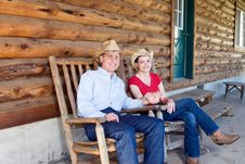 Cowboy And Cowgirl On A Porch - Horizontal Stock Photo