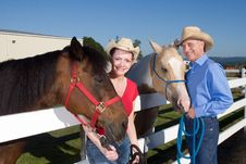 Couple In Cowboy Hats With Horses - Horizontal Royalty Free Stock Photography