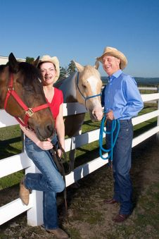 Free Couple In Cowboy Hats With Horses - Vetical Royalty Free Stock Images - 5556279