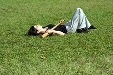 Woman Laying On Grass Holding Bat-Horizontal Royalty Free Stock Image