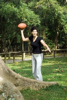 Woman Next To A Tree In A Park Throwing A Footb Stock Image