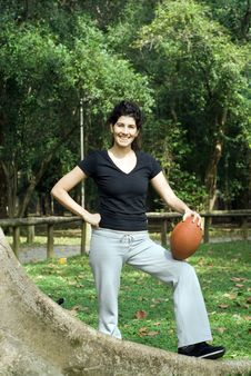 Woman Next To Tree Holding Football - Vertical