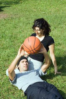 Free Man Holding Basketball Sitting With Woman Stock Photography - 5579722