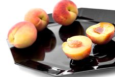 Fresh Peaches With Syrup On A Black Plate Royalty Free Stock Photos