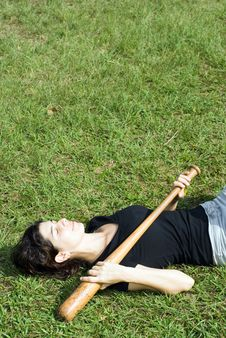 Free Woman Laying In Park With Baseball Bat - Vertical Royalty Free Stock Photography - 5607607