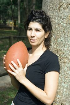 Woman Against Tree Holding Football - Vertical Stock Photography